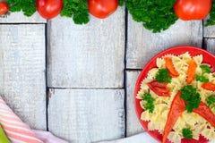 Farfalle végétal végétarien de pâtes avec le tomto, les poivrons et le basilic dans le plat blanc sur la table en bois Vue supéri Images libres de droits