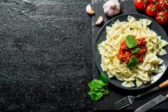 Farfalledeegwaren met Bolognese saus, tomaten, knoflook en muntbladeren stock afbeeldingen