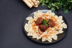 Farfalledeegwaren met Vleesballetjes en Saus op Zwarte Plaat Gezond voedsel Donkere Achtergrond voor exemplaarruimte voor Tekst royalty-vrije stock foto's