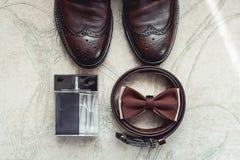 Farfallino di Brown, profumo, scarpe di cuoio e cinghia Governa la mattina di nozze Chiuda su degli accessori dell'uomo moderno Immagini Stock Libere da Diritti