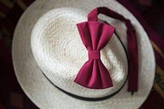 Farfallino maschio rosso su un cappello d'annata di vimini bianco Immagine Stock Libera da Diritti
