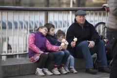 Farfar med barnbarn som äter glass, medan sitta på balustraden på Southbank Arkivbild
