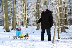 Farfar med barnbarnet som tycker om vinterskogen Royaltyfri Fotografi