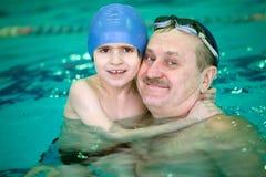 Farfar med den lilla pojken i simbassäng royaltyfri fotografi