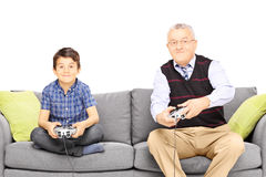 Farfar med hans brorson som placeras på en modern soffa som spelar vide royaltyfria bilder