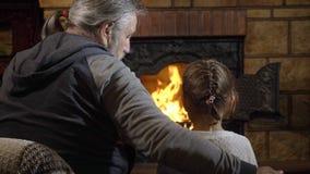 Farfar med hans sondotter som ser på flamman i spis lager videofilmer