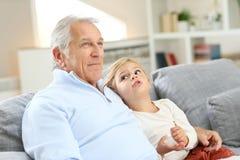 Farfar med sondottern i soffa arkivbilder