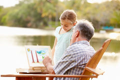 Farfar med sondottern som målar utomhus landskap Arkivbild