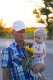 Farfar med sonsonen i hans armar som rymmer en solros Fotografering för Bildbyråer