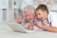 Farfar med sonsonen som använder bärbara datorn, medan ligga på golv royaltyfri fotografi