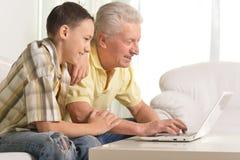 Farfar med sonsonen som hemma använder bärbara datorn arkivbild