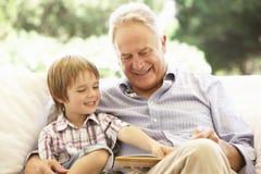 Farfar med sonsonen som tillsammans läser på soffan arkivbilder