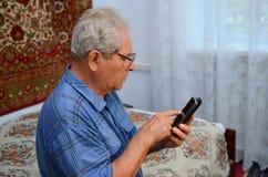 Farfar med telefonen Arkivbild