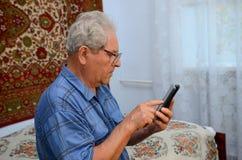Farfar med telefonen Fotografering för Bildbyråer