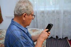 Farfar med telefonen Royaltyfri Bild