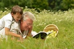 Farfar och barn i skog Arkivfoton