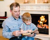 Farfar och barnbarn som läser en bok Arkivbilder