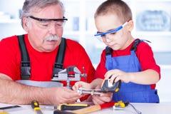 Farfar och barnbarn som mäter bulten Arkivbilder