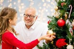 Farfar och sondotter på julträdet royaltyfria foton