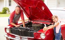 Farfar och sondotter som arbetar på den klassiska bilen Arkivfoto