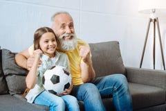 Farfar och sondotter som firar mål av det favorit- laget royaltyfri fotografi