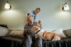 Farfar och sonson med hundsammanträde på soffan i rum fotografering för bildbyråer