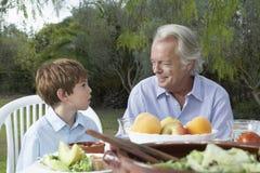 Farfar och sonson på den utomhus- tabellen arkivfoto