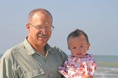 Farfar och sonson på stranden arkivfoto
