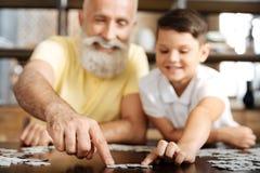 Farfar och sonson som förbinder två stycken av pusslet Arkivfoto