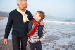 Farfar och sonson som går på vinterstranden Arkivbilder