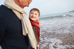 Farfar och sonson som går på vinterstranden Arkivfoto