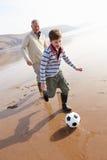 Farfar och sonson som spelar fotboll på vinterstranden royaltyfri bild