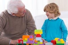 Farfar och sonson som spelar tegelstenar Royaltyfri Bild