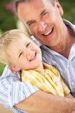 Farfar och sonson som tillsammans kopplar av på sofaen Fotografering för Bildbyråer