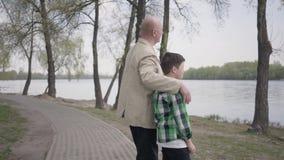 Farfar- och sonsonanseende p? flodstranden som ser p? vattnet Mannen kramar barnet vid hans skuldror arkivfilmer