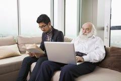Farfar som använder bärbara datorn medan sonsonläsebok på soffan hemma Fotografering för Bildbyråer