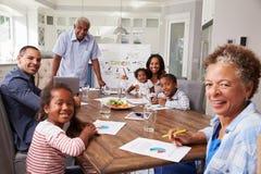 Farfar som framlägger ett hem- möte, familj som ser till kameran royaltyfria bilder