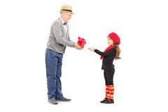 Farfar som ger gåva till hans lilla brorsdotter Royaltyfri Bild