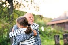 Farfar som ger hans grandaughter en kram Royaltyfria Bilder