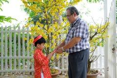 Farfar som ger lyckliga pengar till sonsonen på den första dagen av det vietnamesiska mån- nya året Tet arkivfoto