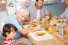 Farfar som hjälper sonsonen, medan ha frukosten Royaltyfri Bild