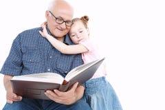 Farfar som läser en bok med sondottern Arkivfoto