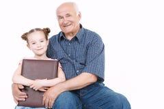 Farfar som läser en bok med sondottern Royaltyfri Foto