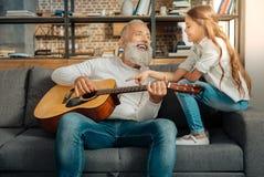 Farfar som pratar med sondottern, medan rymma gitarren arkivfoton
