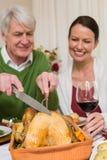 Farfar som snider höna medan kvinna som dricker rött vin Royaltyfri Foto