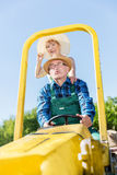 Farfar som tar farmodern för ritt på traktorsläpet över bygd Royaltyfri Foto