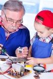 Farfar som visar PCB som löder till barnbarnet Royaltyfria Foton
