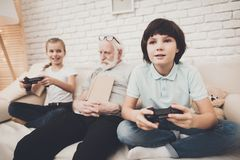 Farfar, sonson och sondotter hemma Barn spelar videospel, och morfadern sover royaltyfri fotografi