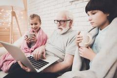 Farfar, sonson och sondotter hemma Morfadern och barn håller ögonen på film och dricker te arkivbild