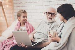 Farfar, sonson och sondotter hemma Morfadern och barn håller ögonen på film och dricker te royaltyfri fotografi